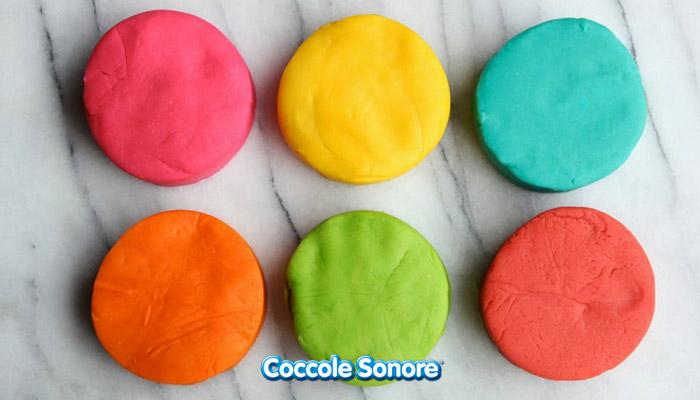 panetti di pongo fatto in casa rosa, giallo, verde, arancione, azzurro, rosso su tavola di marmo, coccole sonore