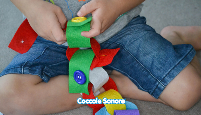 bambino gioca con catena di feltro montessori