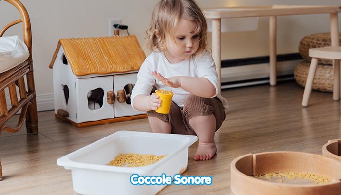bambina gioca con i travasi montessori