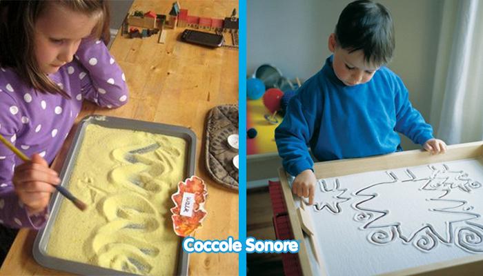 bambini giocano con lavagna di sabbia montessori