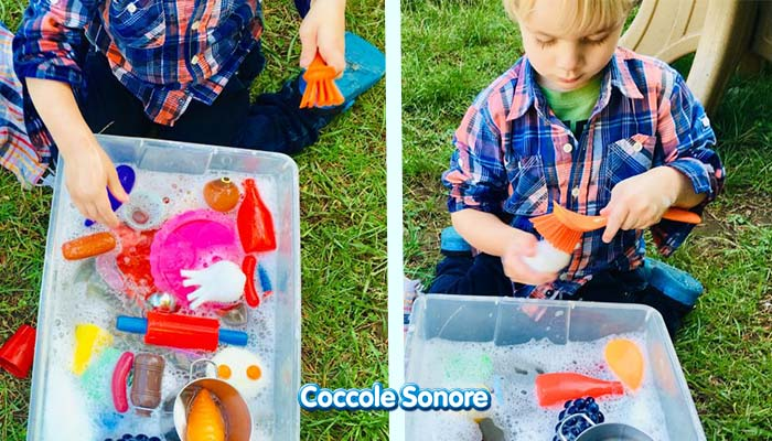 bambino gioca con un contenitore sensoriale per lavare i piatti e le verdure con metodo montessori